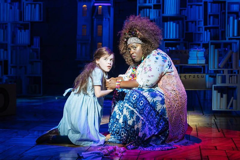 Matilda and another cast member holding hands on stage at Matilda The Musical.