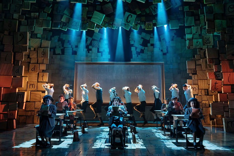 The child cast on stage at Matilda The Musical in a classroom dance sequence.