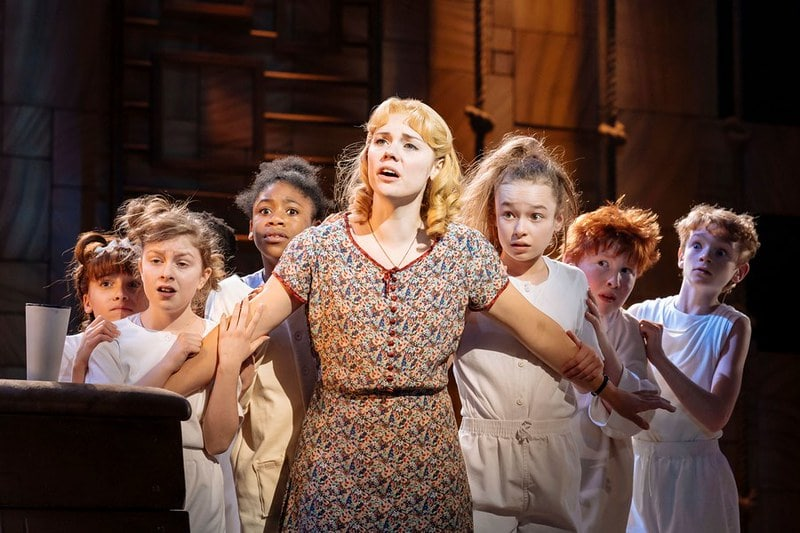 Miss Honey shielding a group of children on stage at Matilda The Musical.