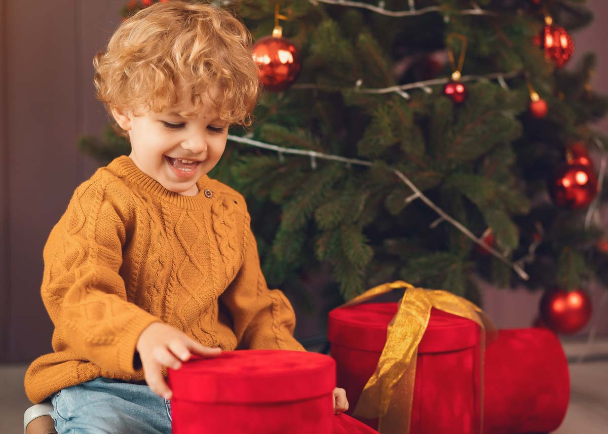 Little boy sat by the Christmas tree smiling looking at his Christmas presents.