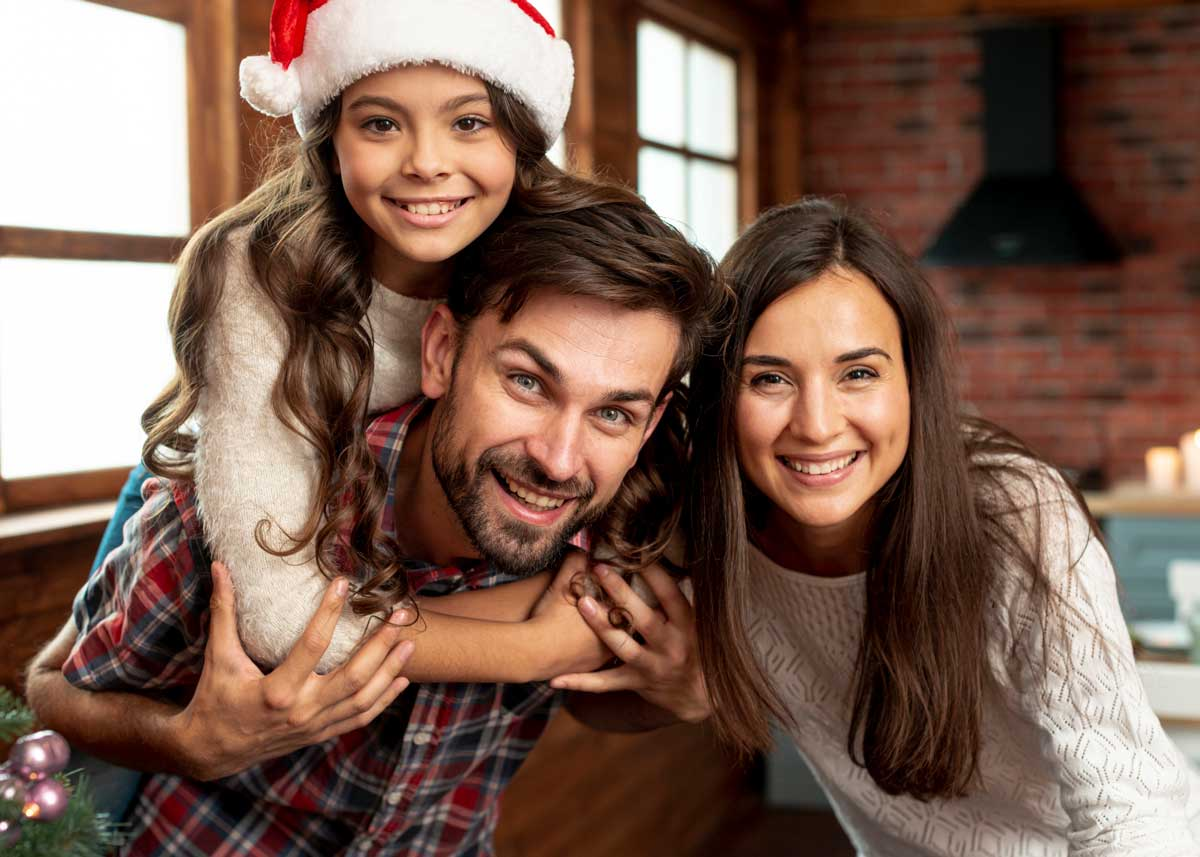 Young girl wearing a Santa hat hugging her dad while she smiles for a Christmas photo with her parents.