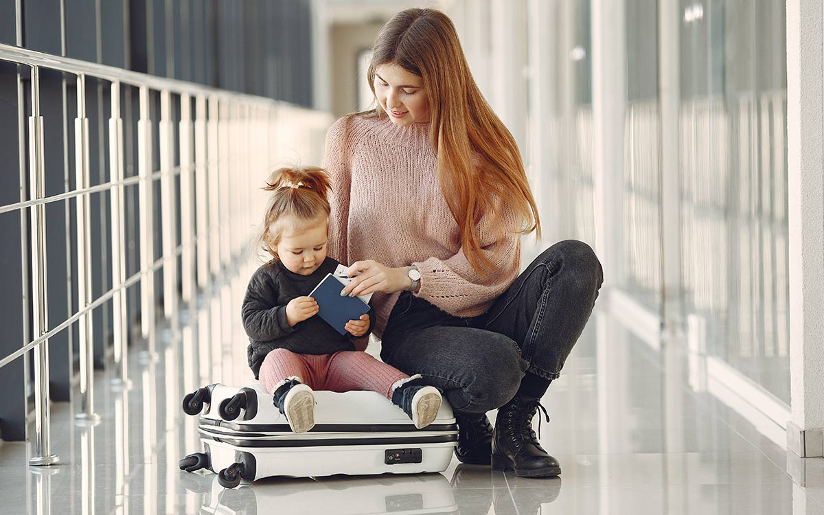 Mum crouching next to her young toddler who is sat on the suitcase at the airport.