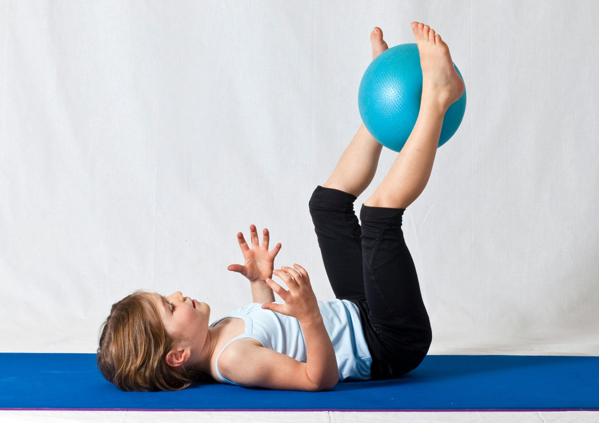 A young sporty girl is lying on her back on a yoga mat lifting a ball into the air with her feet.