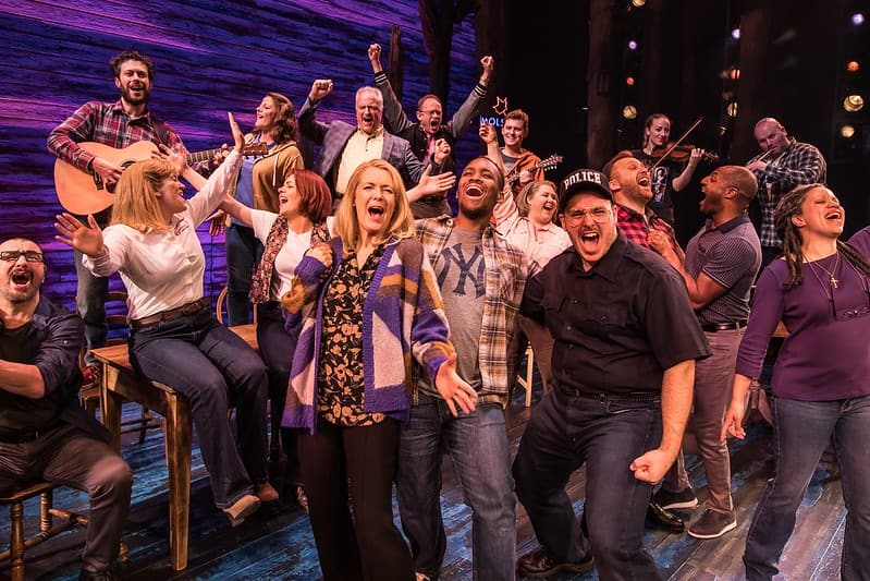 The cast of Come From Away in a group on stage singing a lively song.