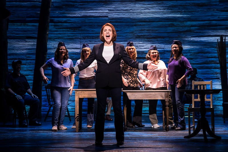 A character from Come From Away singing a song on stage wearing a suit.