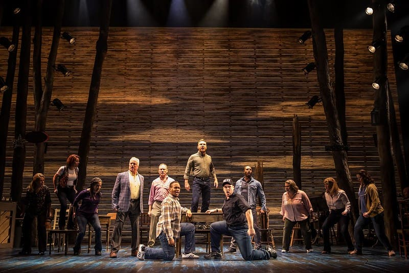 The cast of Come From Away singing a dramatic song on stage with some characters kneeling in the foreground.