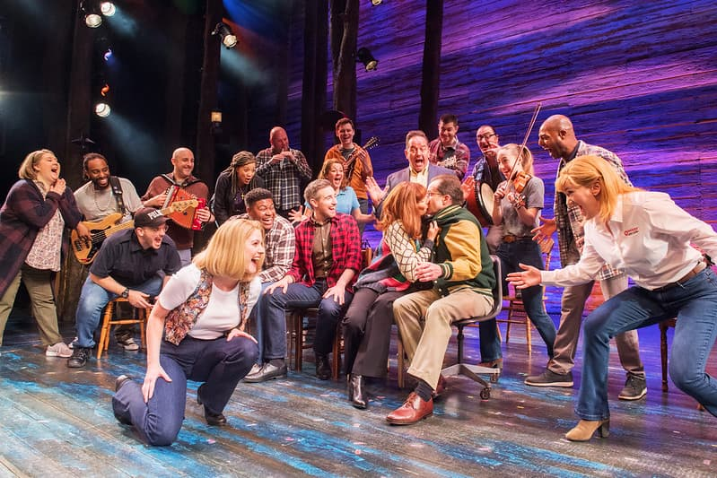 Two characters from Come From Away kissing on stage with the rest of the cast cheering around them.