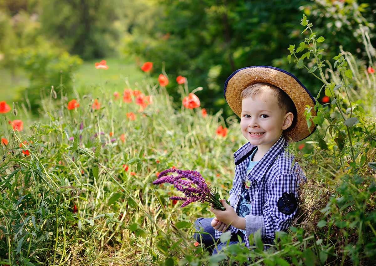 Young boy sitting in the country, he is wearing a straw hat and is surrounded by colourful flowers.