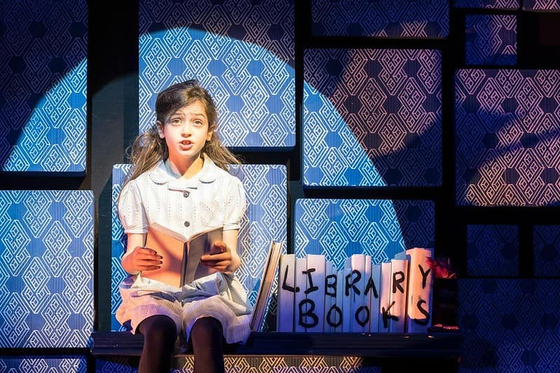 The main character Matilda sitting with a book singing in a spotlight in Matilda the Musical.