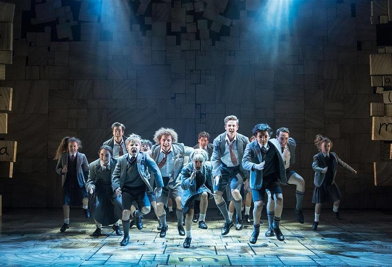 The child cast on stage at Matilda The Musical in a dance sequence.