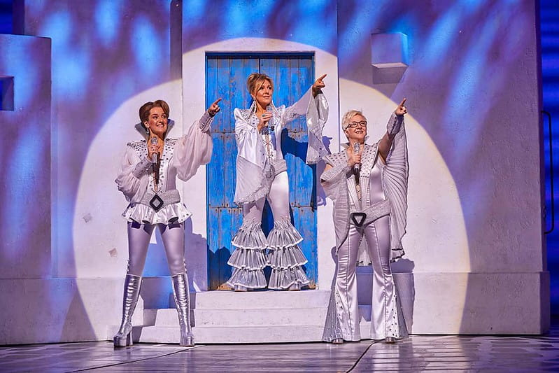 Donna and the Dynamos performing a song on stage in Mamma Mia wearing white ABBA costumes.