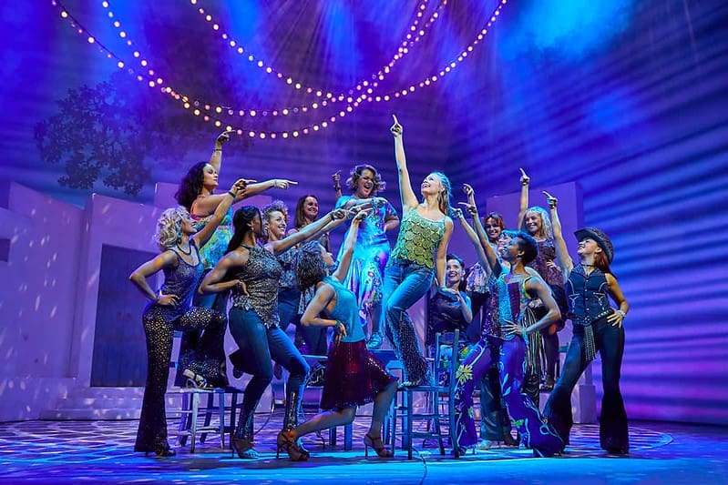 The cast on stage at Mamma Mia performing a song with Sophie in the middle of a group of friends.