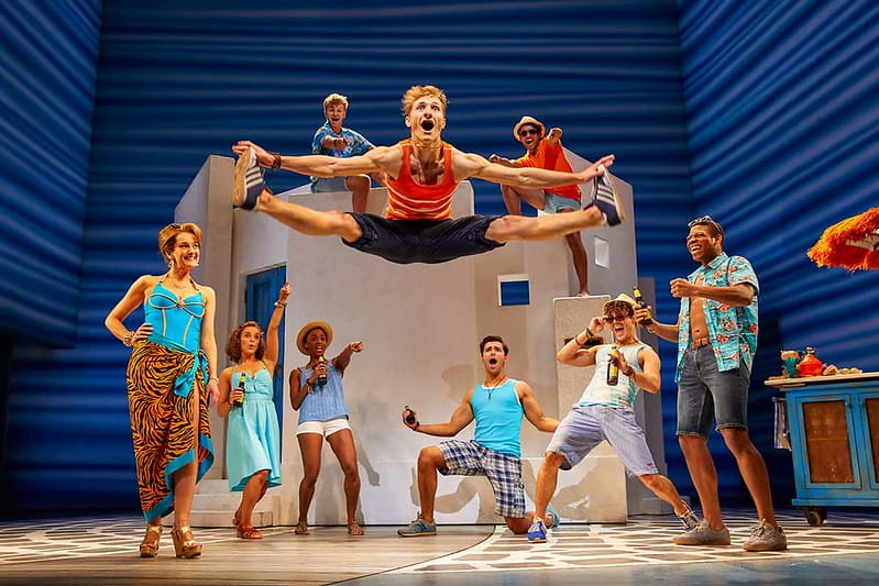 A dance number from Mamma Mia with one character doing a high straddle jump in the air.