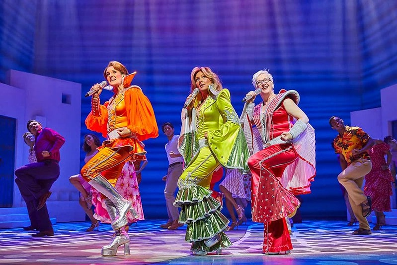 The cast of Mamma Mia performing a song wearing bright ABBA costumes.