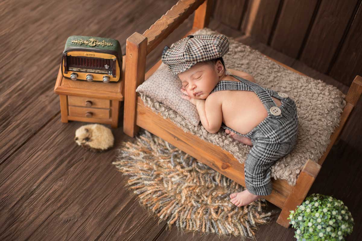 A baby boy is lying on his front, asleep on a miniature bed and wearing a checked hat.