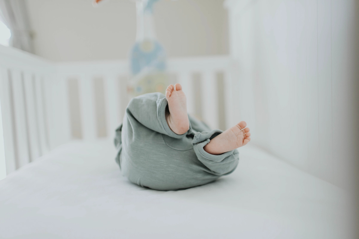 An image of a baby's feet, the baby is lying on its back in a white crib.