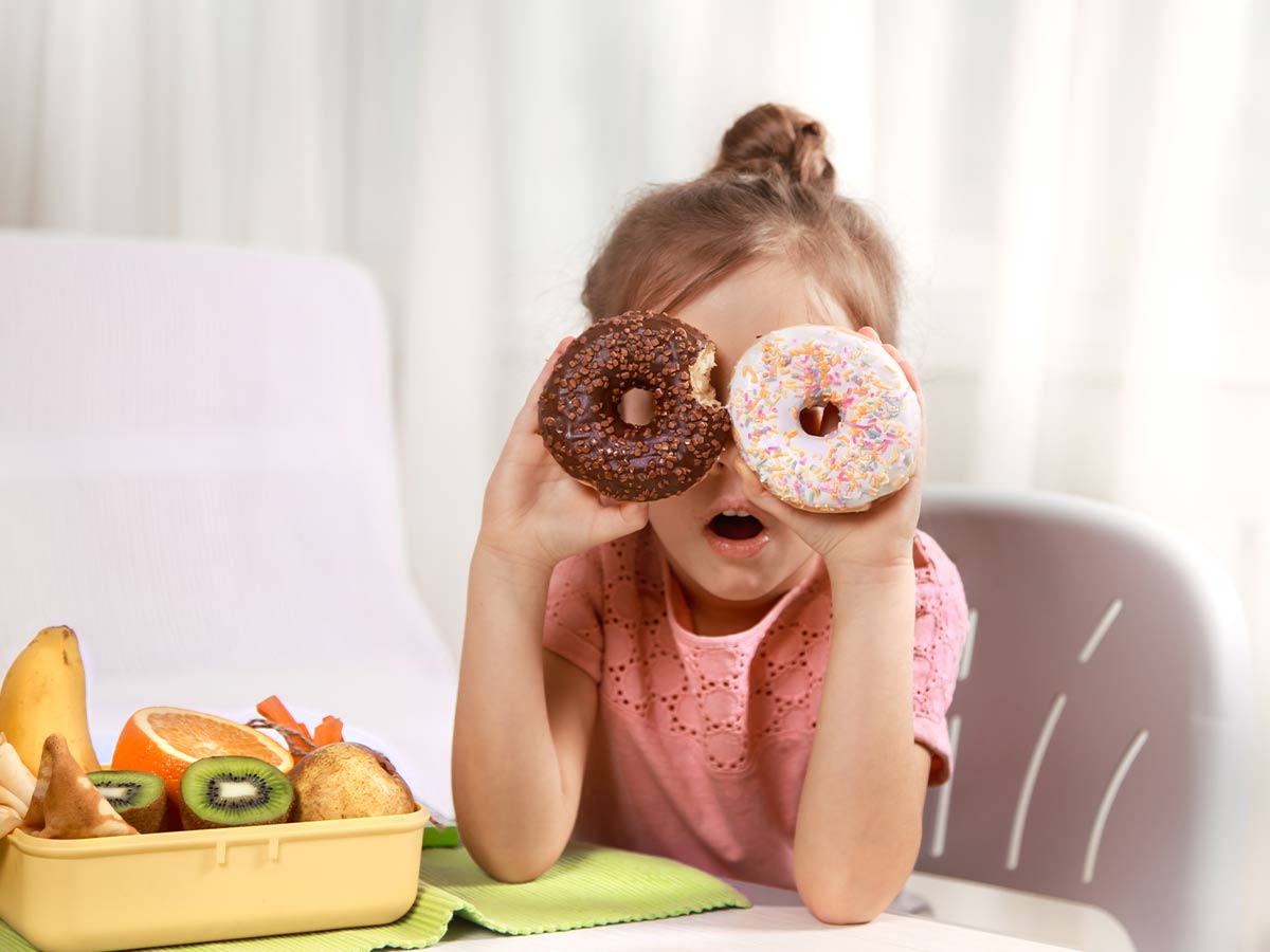 Little girl sat at the table holding up two doughnuts in front of her eyes making a silly face.