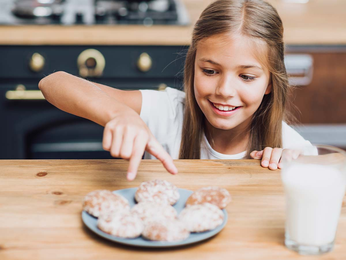 Girl smiling as she is about to take a cookie from the plate.
