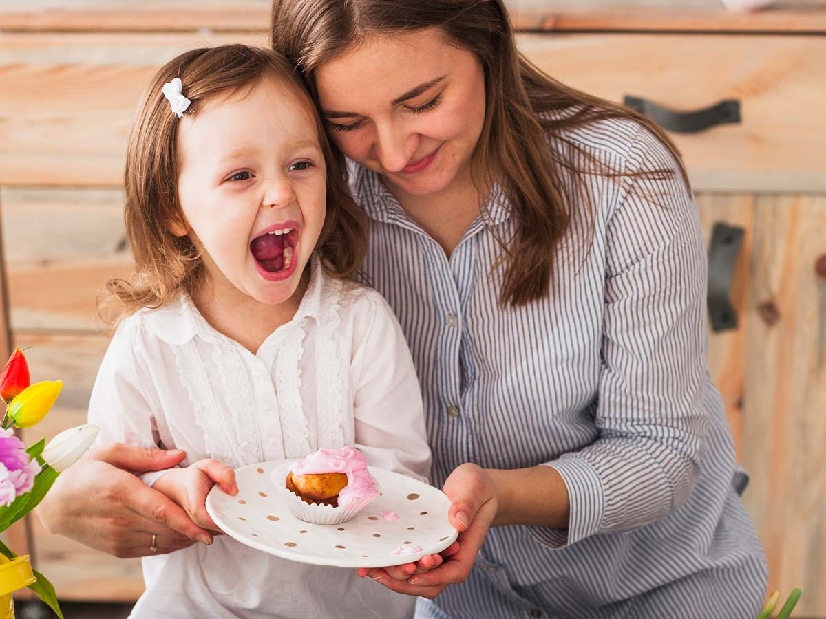 Mum hugging her daughter who is holding a plate of cake and laughing at baking puns.