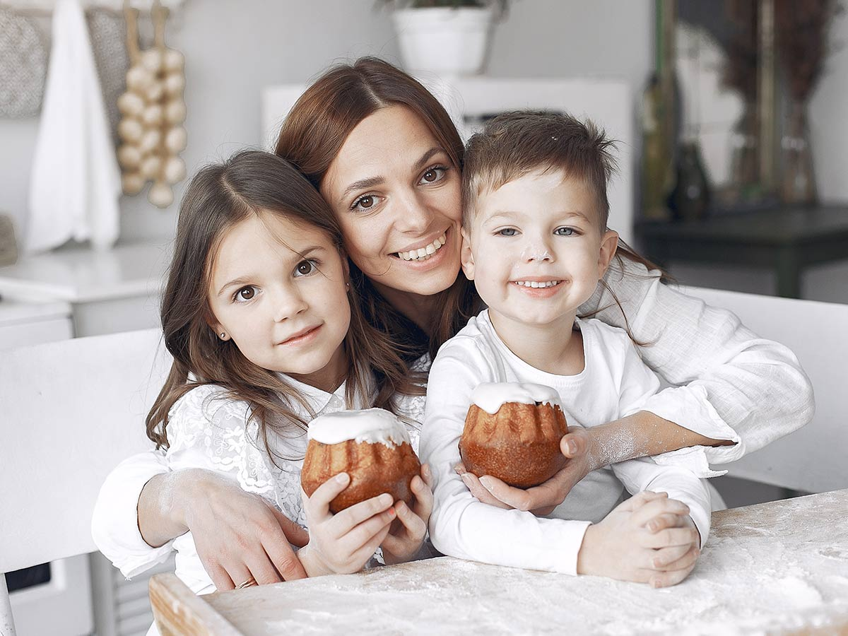 Mum smiling with her two kids who are each holding a little cake..