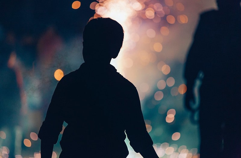 Silhouette of a boy looking on at a crackling bonfire for Bonfire Night.