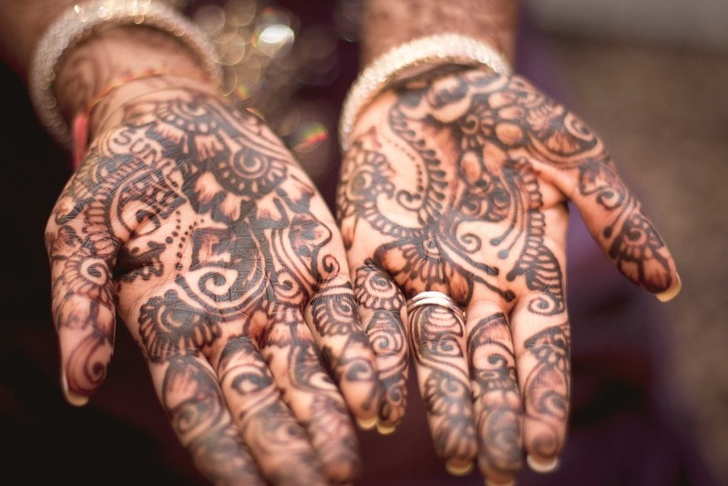 Two hands held out palms facing upwards to show off their intricate henna work.