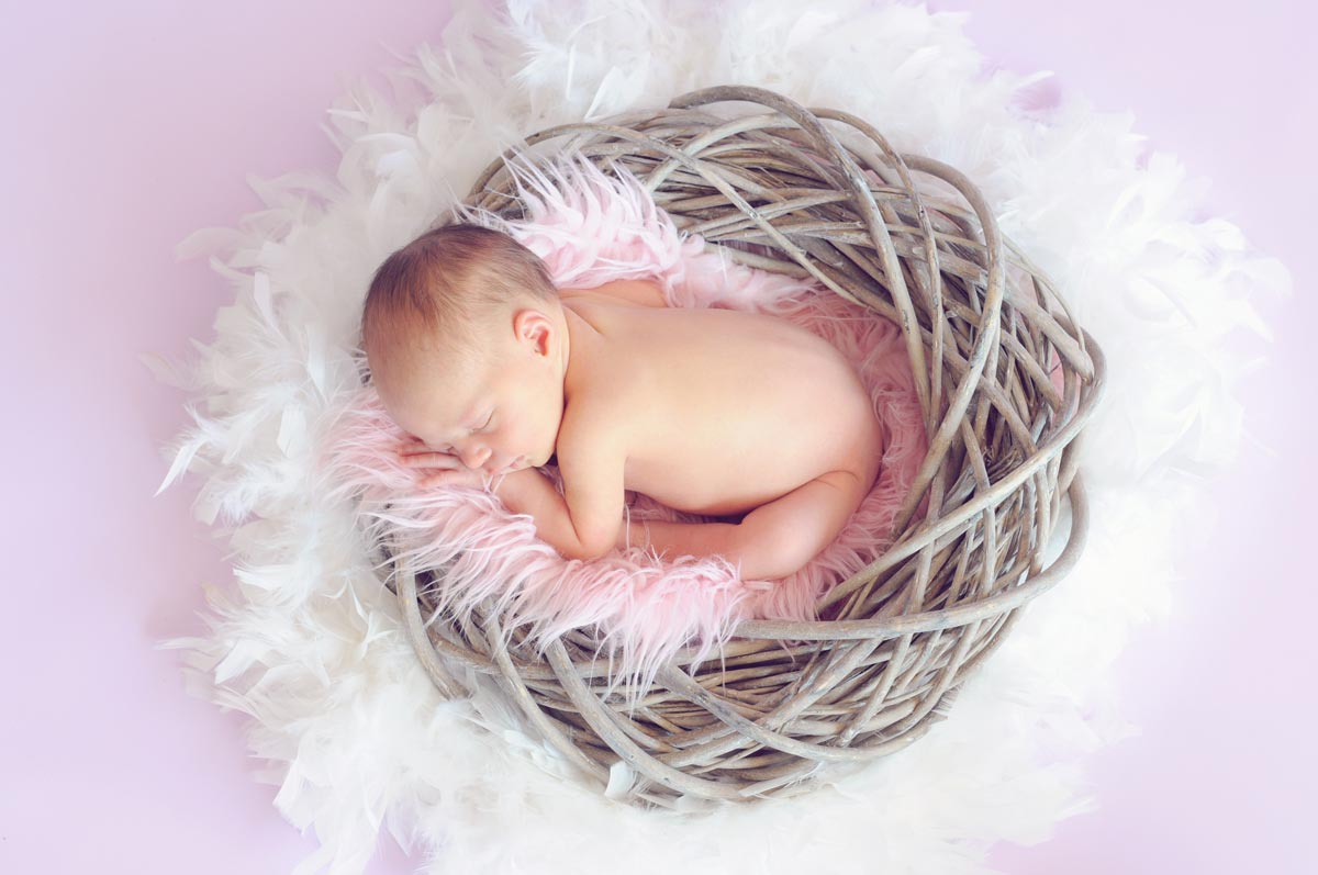 A baby girl is curled up asleep in a basket with a fluffy pink blanket.