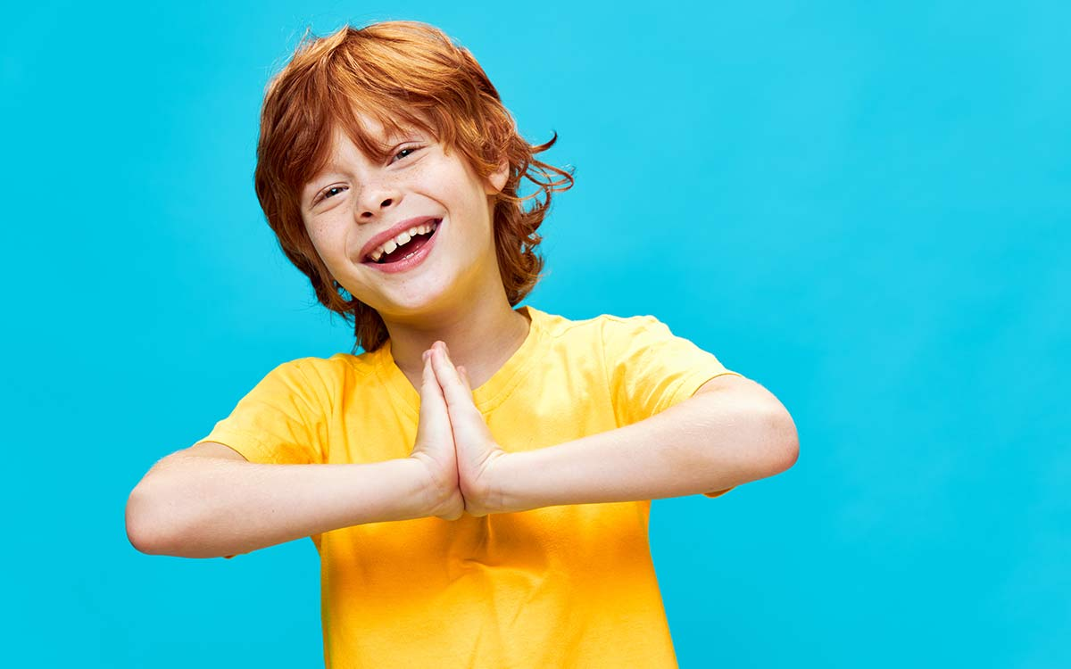 Young boy wearing a yellow t shirt smiling with his hands together standing in front of a blue background.