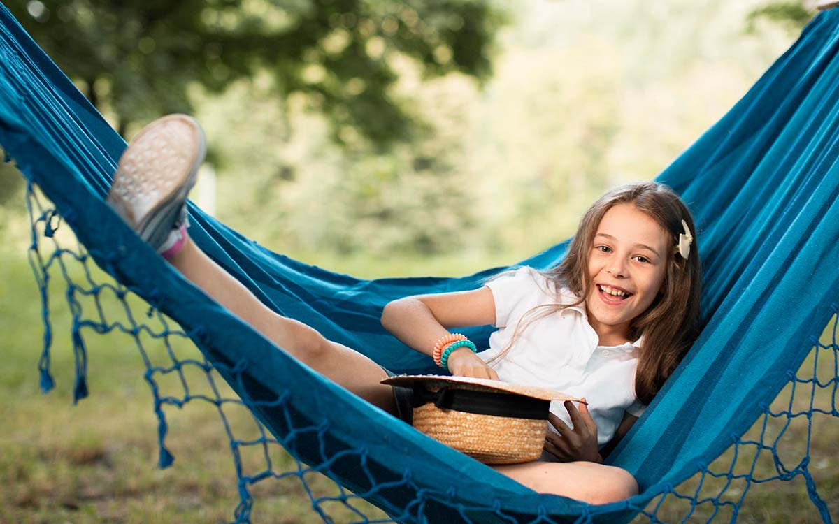 Young girl smiling as she lies in a hammock trying to solve impossible riddles.