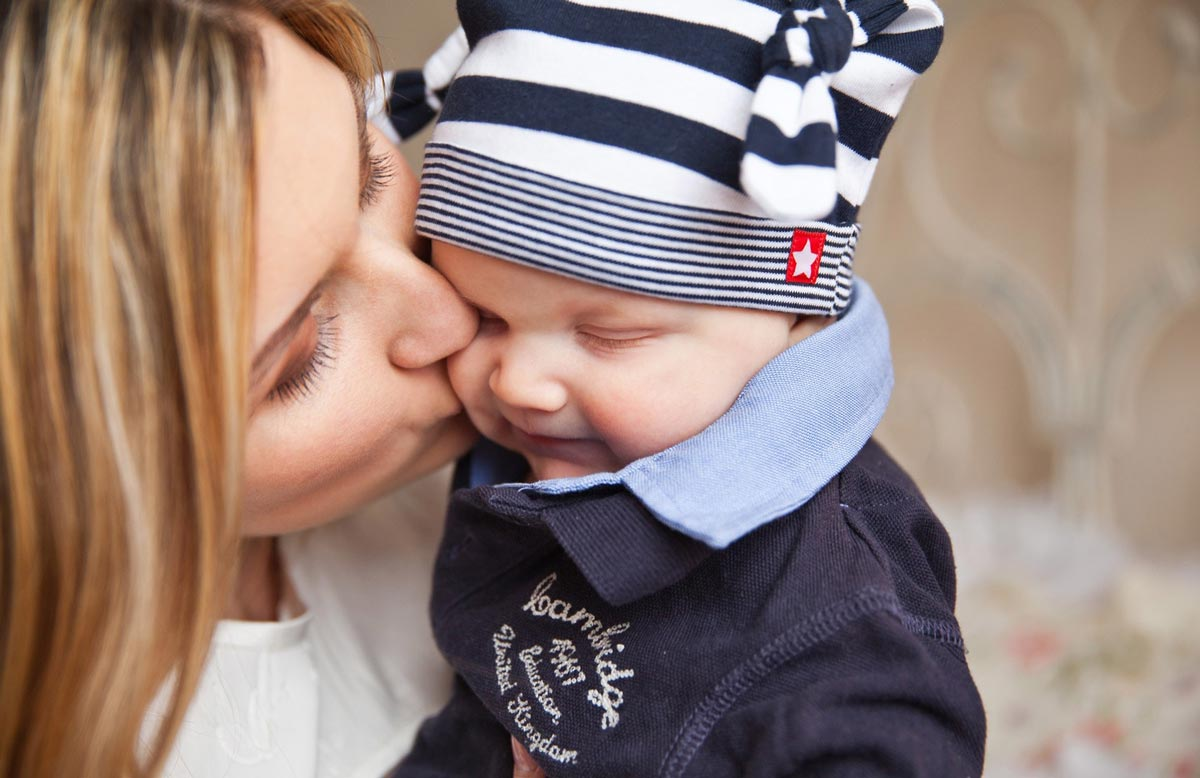 A close up image of a mum holding her baby boy as she kisses his cheek.