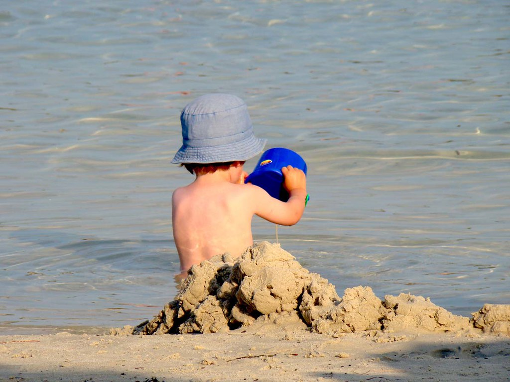 An image from behind of a young boy building a sandcastle and looking out to sea.a