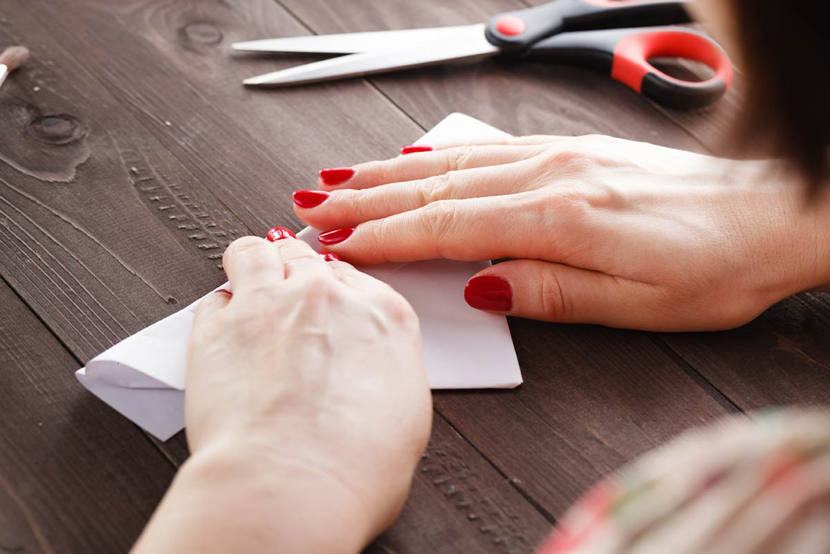 Close up of a woman with red nail polish folding a white piece of paper to make an origami sheep.