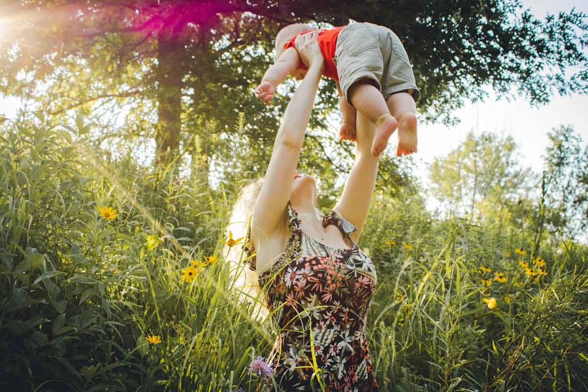 A mother lifts her baby into the air outside at springtime, they are sat outside surrounded by colourful spring flowers.