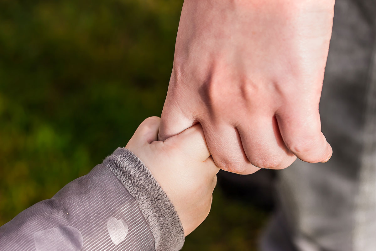 A close up image of a small baby's hand holding an adult's hand.