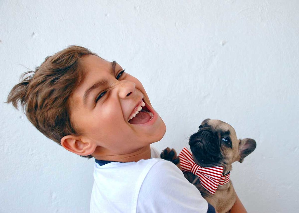 A boy looks at the camera and laughs out loud at a New Year joke whilst holding a puppy.