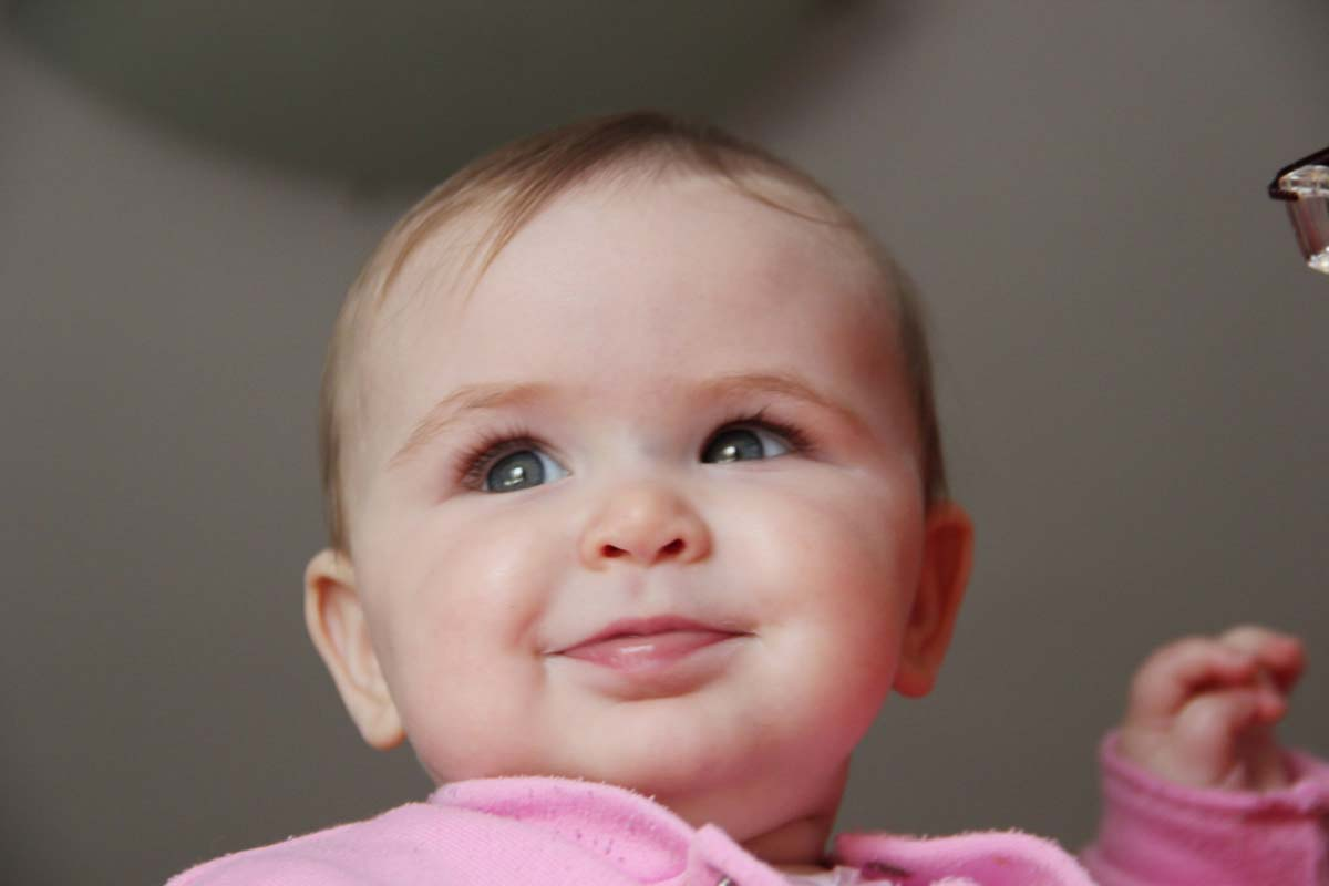 A young baby girl wearing a pink jumper looking beyond the camera.