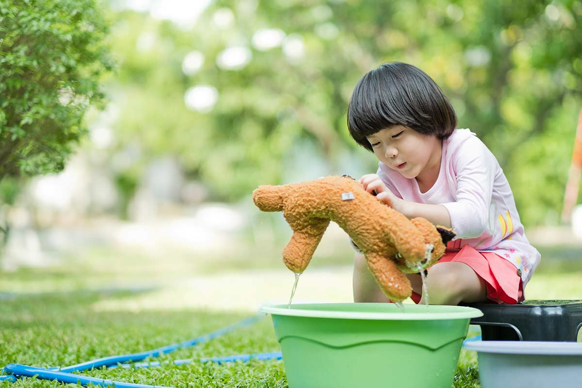 Little girl sat outside cleaning her teddy bear in a bucket of water.
