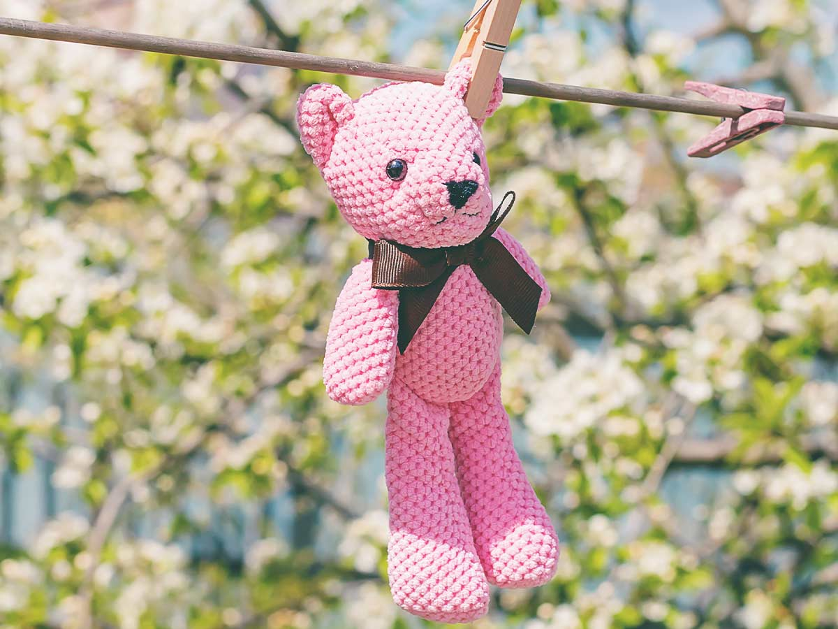 Pink teddy bear air drying on the washing line after being washed.