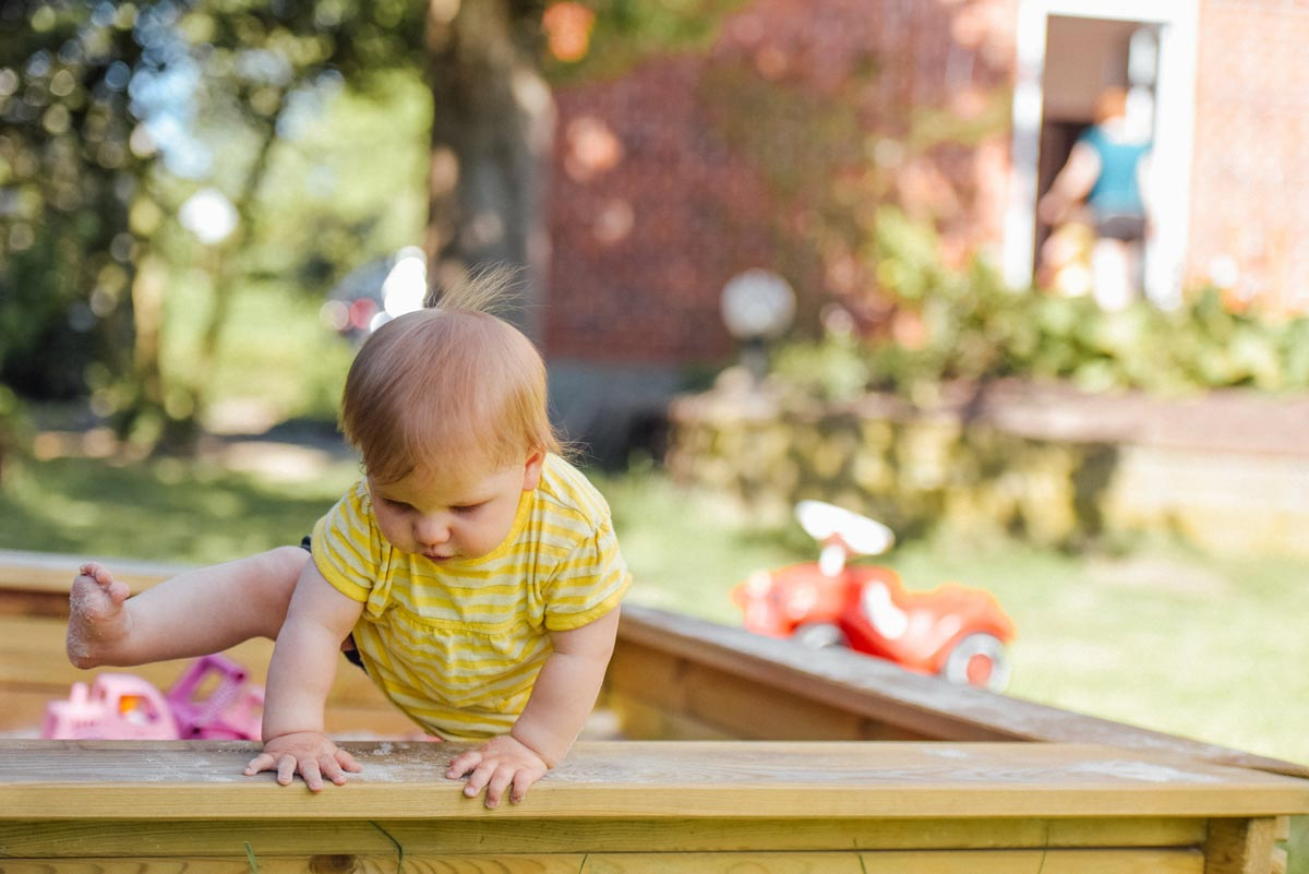 A brave baby girl climbs out of a large sandpit in the garden..