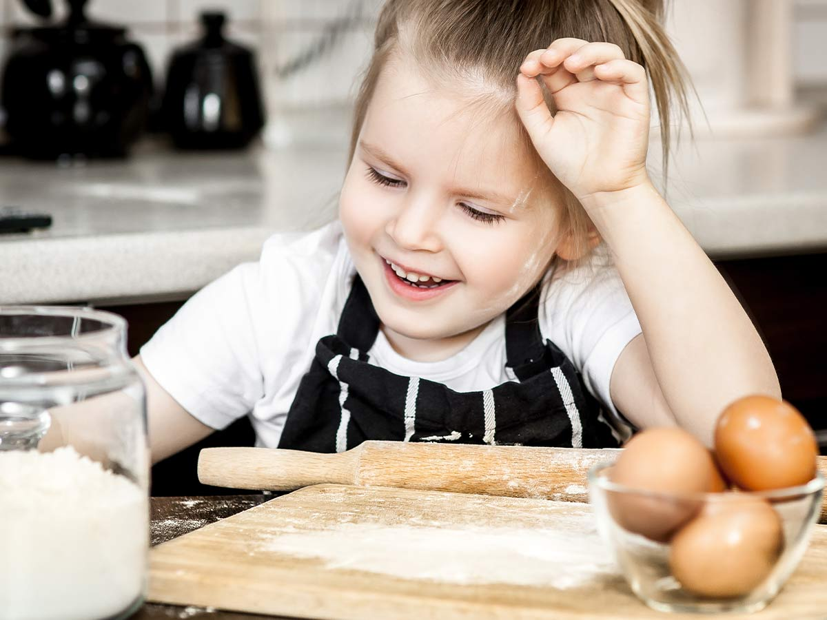 Little girl in the kitchen with flour on her face as she helps her mum make a monkey cake.