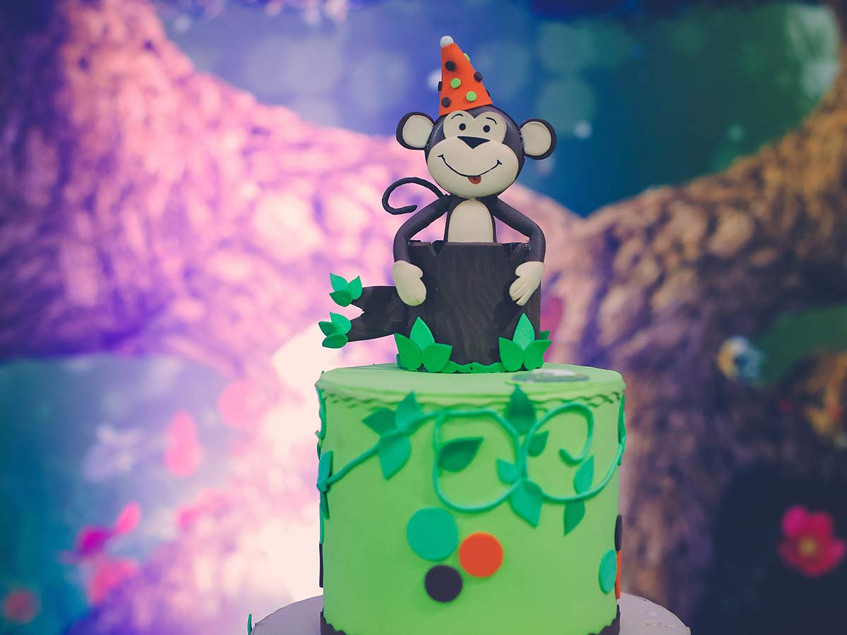 Green birthday cake with a monkey topper.