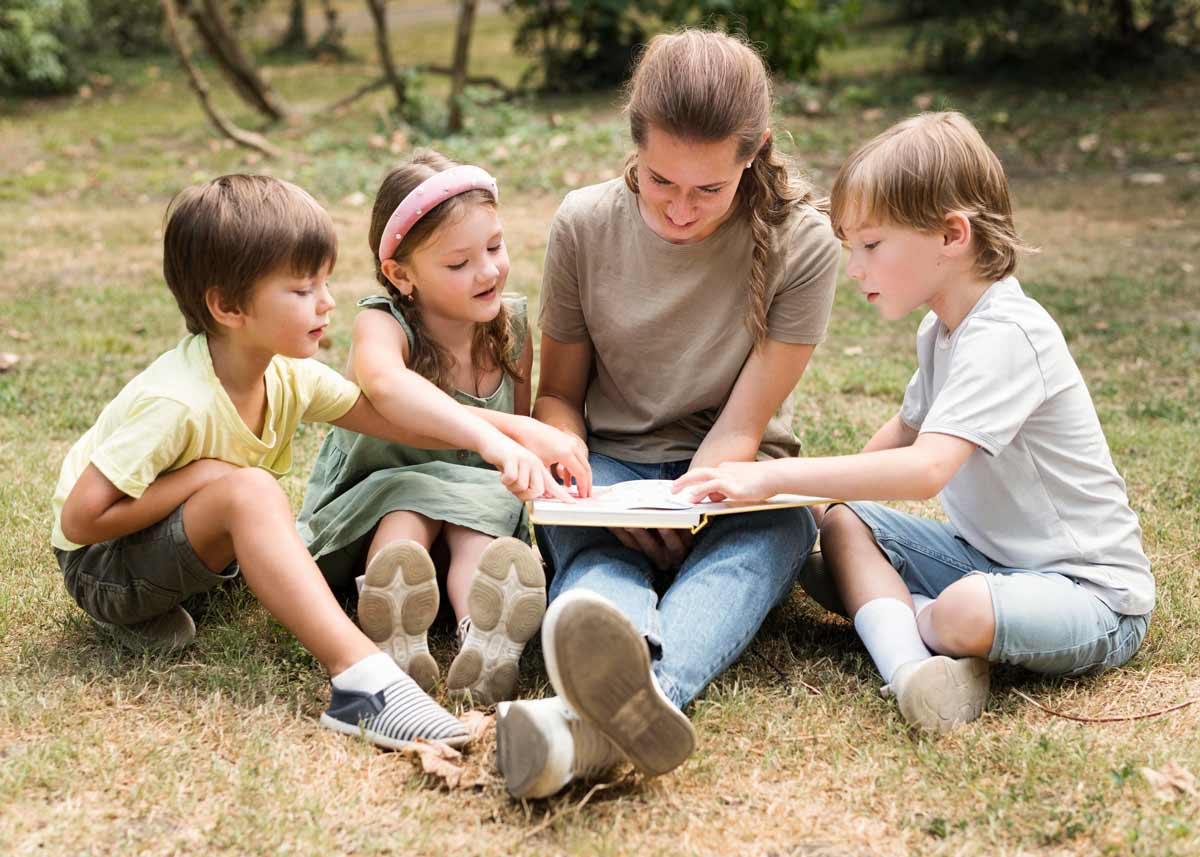 Mum and three kids sat on the grass outside reading a book together.