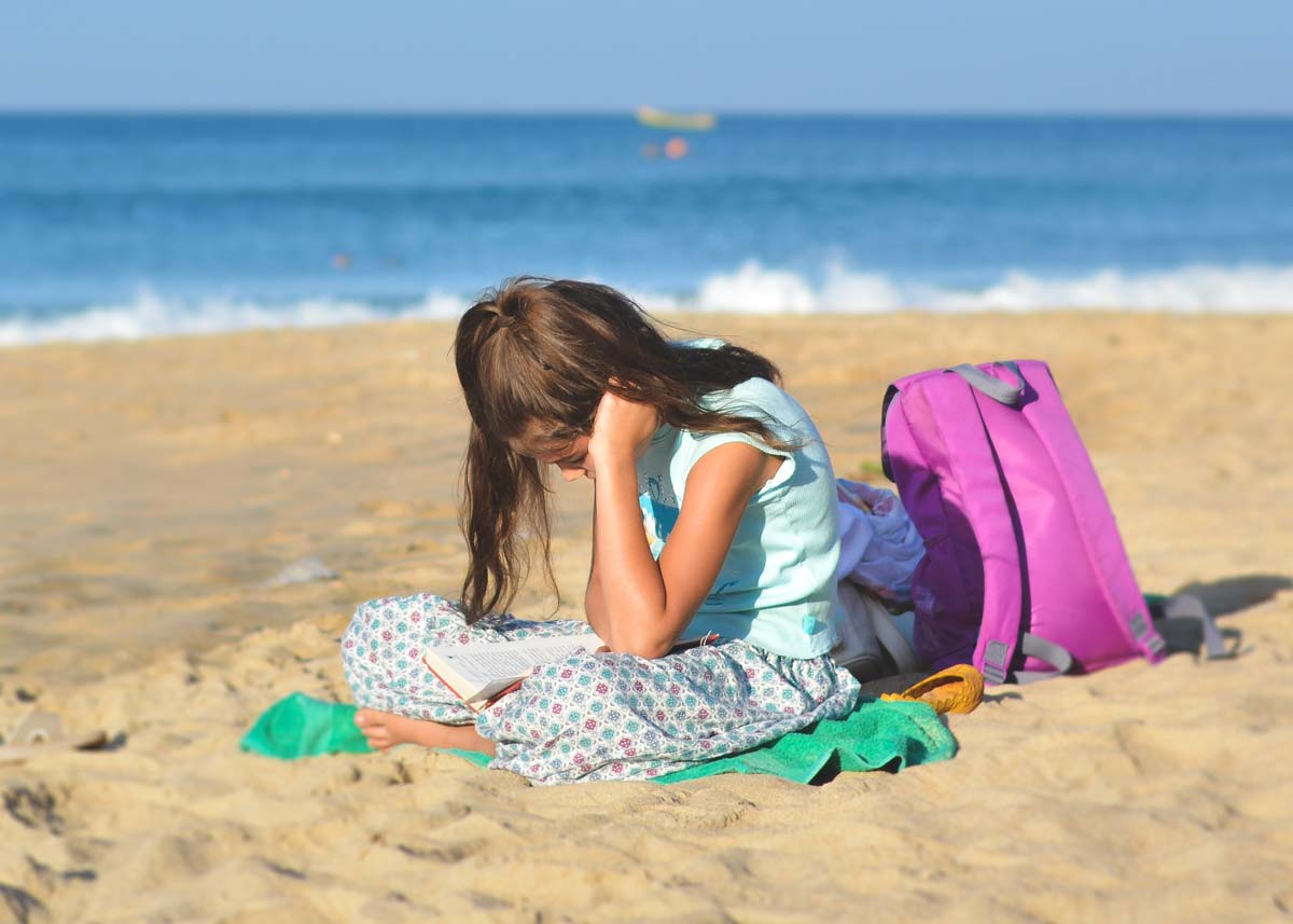 Little girl sat in the sand on the beach reading her book.