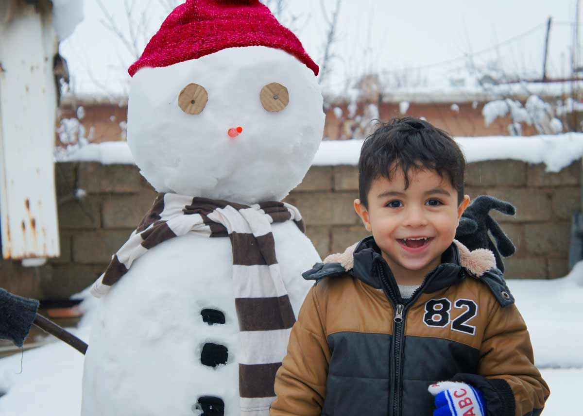Little boy grinning as he stands proudly in front of his snowman.
