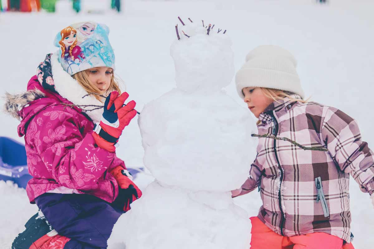 Two girls wrapped up in warm clothing playing outside in the snow building a snowman.