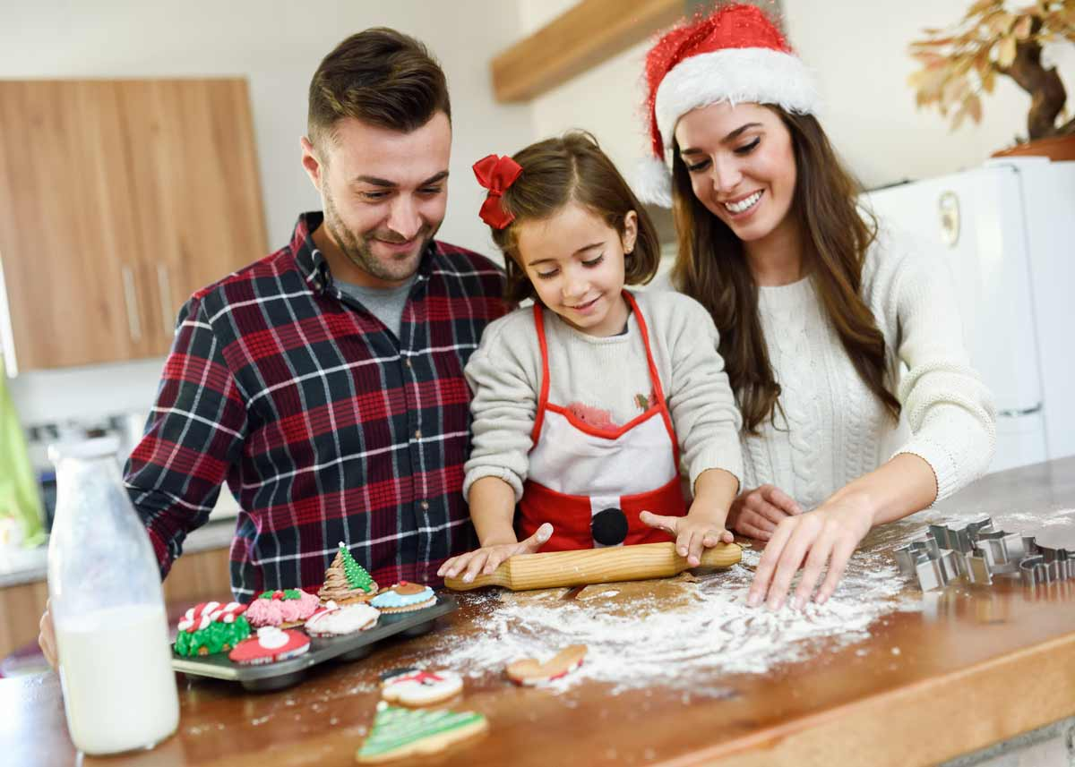 Parents making festive Christmas cookies in the kitchen with their daughter, smiling.