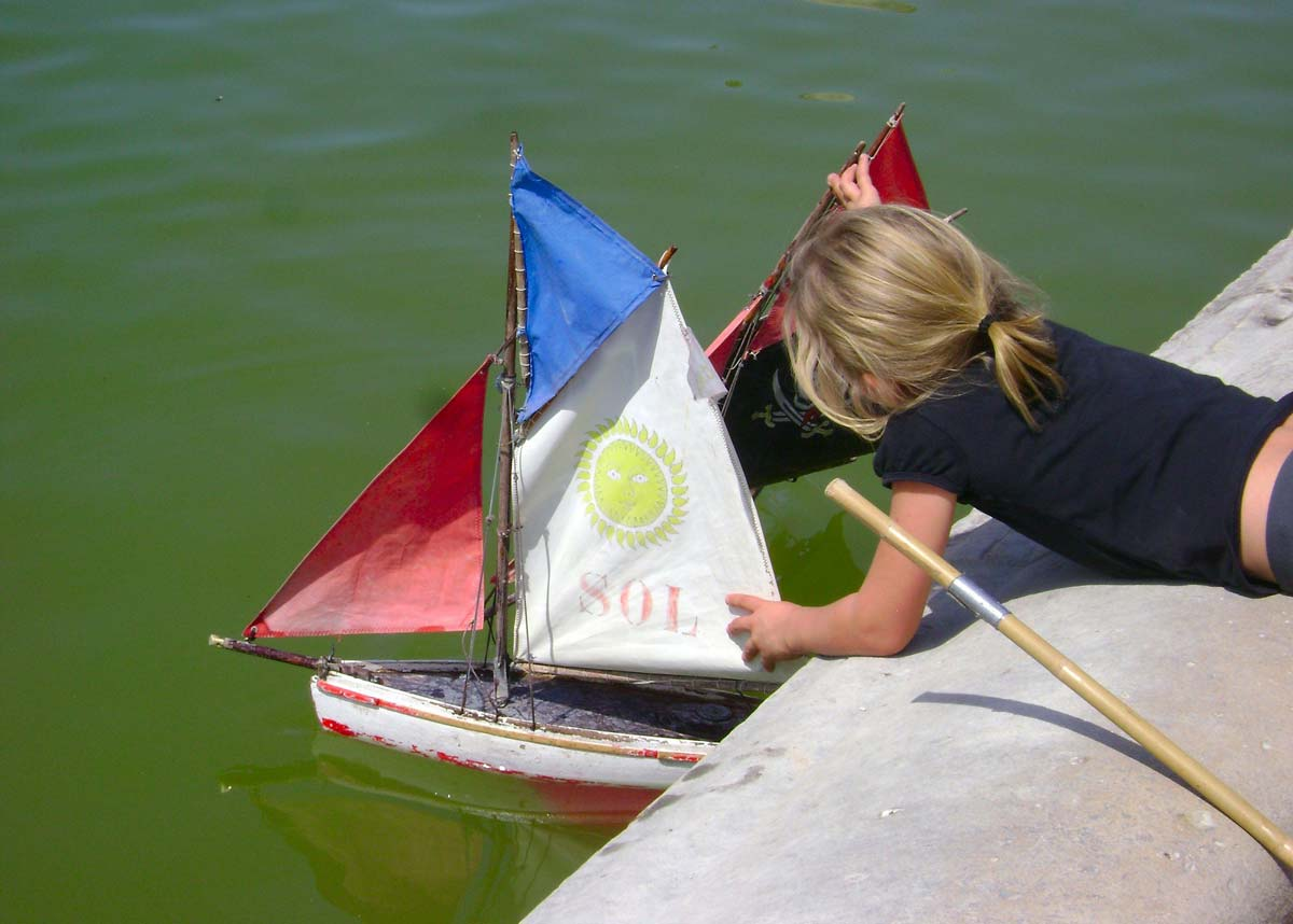 Little girl leaning over the side of a lake to put a miniature sailboat in the water.
