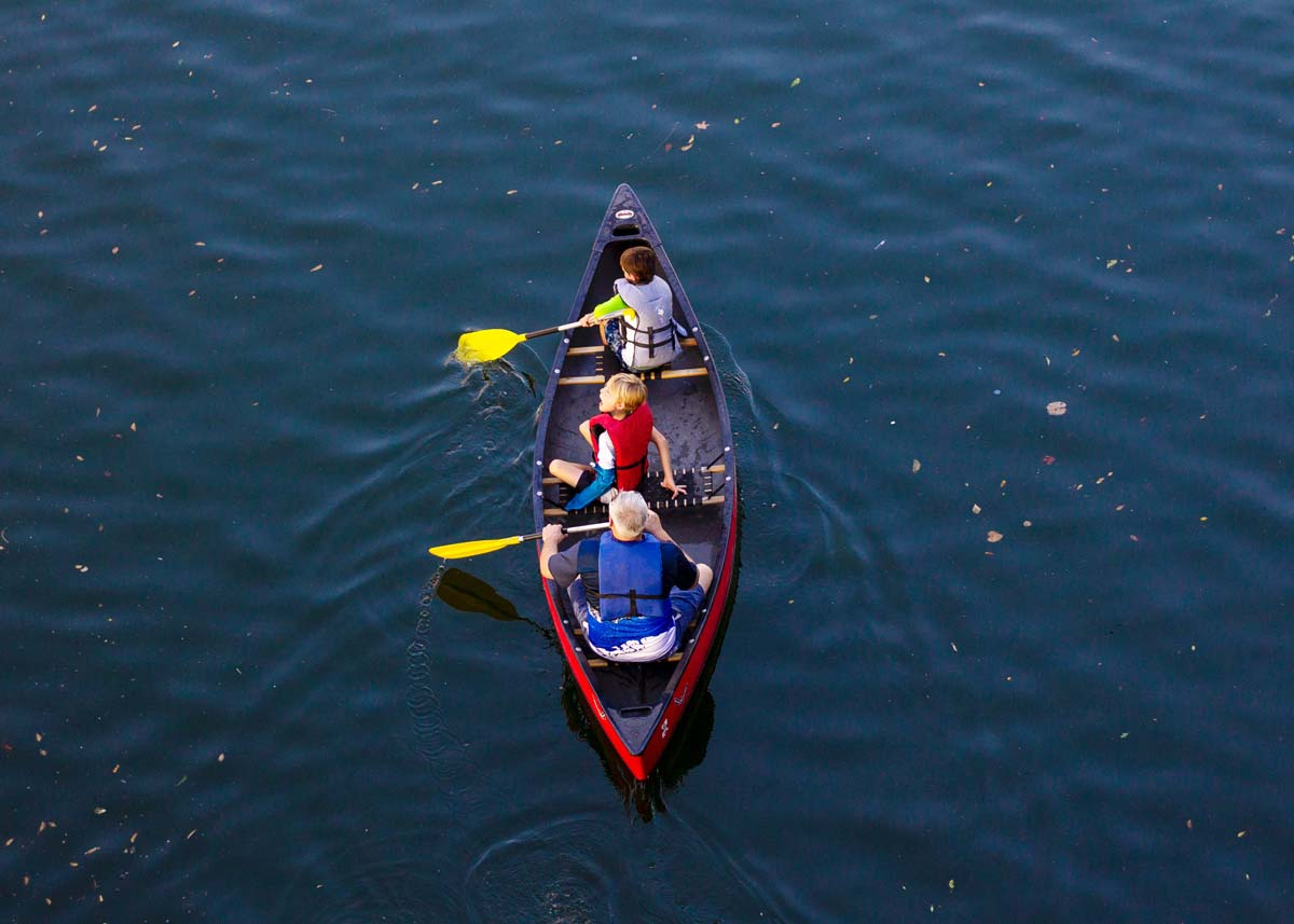 Three boys wearing life vests as they row on the water in a canoe.