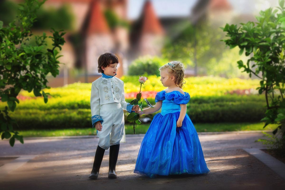 A young boy and girl are standing next to each other wearing fairy tale outfits.