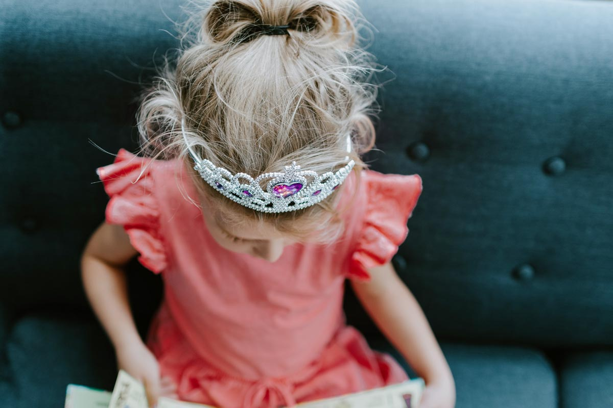 A little girl wearing a princess crown is reading a fairy tale.